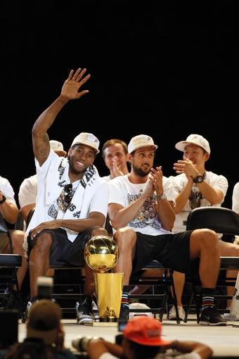 Jun 18, 2014; San Antonio, TX, USA; San Antonio Spurs forward Kawhi Leonard (left) waves to the crowd during NBA championship celebrations at Alamodome. Mandatory Credit: Soobum Im-USA TODAY Sports
