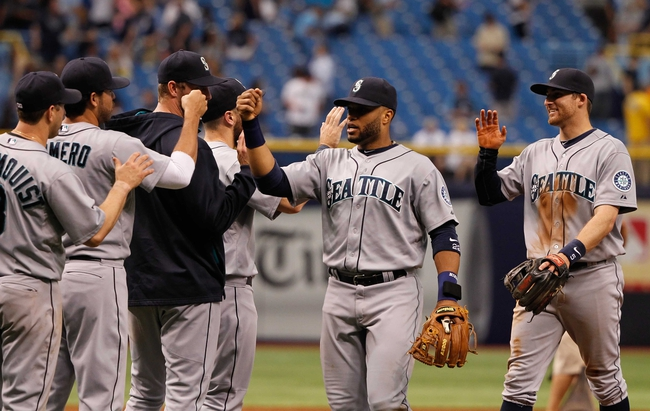 Jun 8, 2014; St. Petersburg, FL, USA; Seattle Mariners second baseman Robinson Cano (22) and teammates high five after they beat the Tampa Bay Rays at Tropicana Field. Seattle Mariners defeated the Tampa Bay Rays 5-0. Mandatory Credit: Kim Klement-USA TODAY Sports