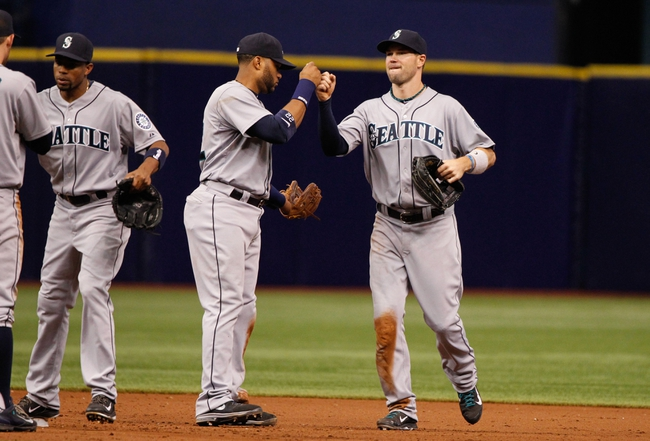 Jun 8, 2014; St. Petersburg, FL, USA; Seattle Mariners second baseman Robinson Cano (22), left fielder Cole Gillespie (16) and teammates high five after they beat the Tampa Bay Rays at Tropicana Field. Seattle Mariners defeated the Tampa Bay Rays 5-0. Mandatory Credit: Kim Klement-USA TODAY Sports