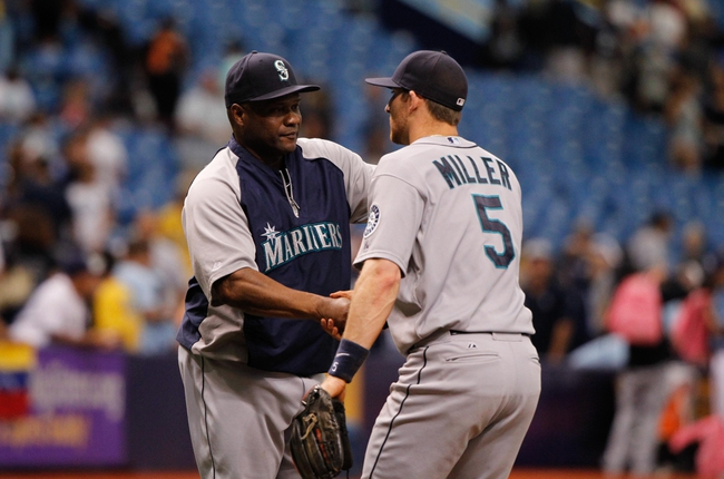Jun 8, 2014; St. Petersburg, FL, USA; Seattle Mariners manager Lloyd McClendon (23) and shortstop Brad Miller (5) hand shake after they beat the Tampa Bay Rays at Tropicana Field. Seattle Mariners defeated the Tampa Bay Rays 5-0. Mandatory Credit: Kim Klement-USA TODAY Sports