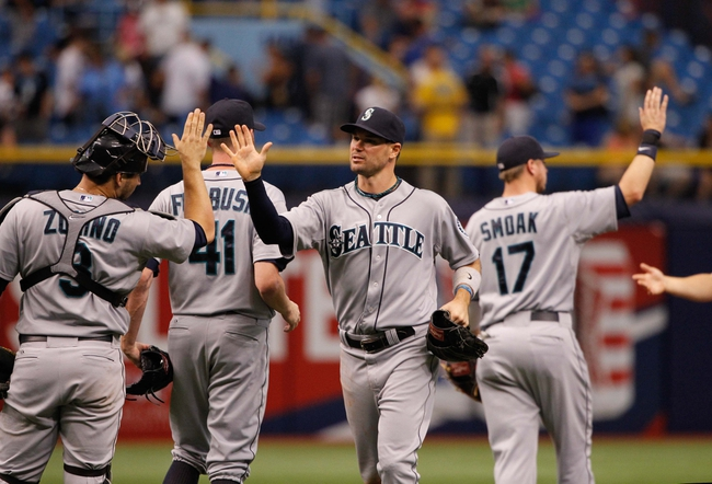 Jun 8, 2014; St. Petersburg, FL, USA; Seattle Mariners left fielder Cole Gillespie (16), catcher Mike Zunino (3) and teammates high five after they beat the Tampa Bay Rays at Tropicana Field. Seattle Mariners defeated the Tampa Bay Rays 5-0. Mandatory Credit: Kim Klement-USA TODAY Sports