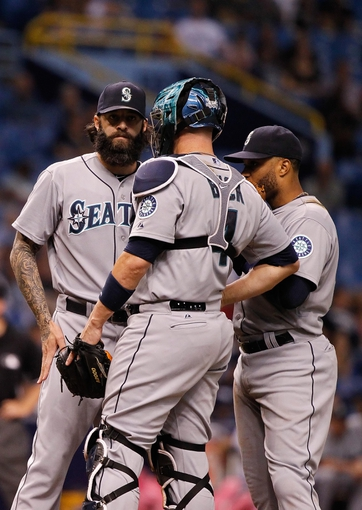 Jun 6, 2014; St. Petersburg, FL, USA; Seattle Mariners relief pitcher Joe Beimel (97) talks with catcher John Buck (4) and second baseman Robinson Cano (22) on the mound against the Tampa Bay Rays at Tropicana Field. Mandatory Credit: Kim Klement-USA TODAY Sports