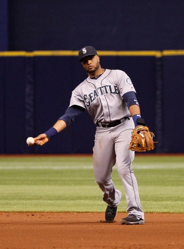 Jun 6, 2014; St. Petersburg, FL, USA;Seattle Mariners second baseman Robinson Cano (22) throws the ball to first for an out against the Tampa Bay Rays at Tropicana Field. Tampa Bay Rays defeated the Seattle Mariners 4-0. Mandatory Credit: Kim Klement-USA TODAY Sports