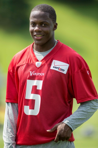 Jun 17, 2014; Eden Prairie, MN, USA; Minnesota Vikings quarterback Teddy Bridgewater (5) talks with a coach at Winter Park. Mandatory Credit: Bruce Kluckhohn-USA TODAY Sports