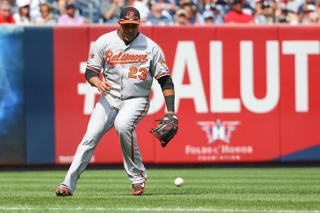 Jun 22, 2014; Bronx, NY, USA;  Baltimore Orioles left fielder Nelson Cruz (23) fields a ball during the fifth inning against the New York Yankees at Yankee Stadium. Baltimore Orioles won 8-0. Mandatory Credit: Anthony Gruppuso-USA TODAY Sports