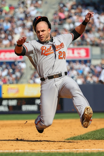 Jun 22, 2014; Bronx, NY, USA;  Baltimore Orioles first baseman Steve Pearce (28) slides into third during the eighth inning against the New York Yankees at Yankee Stadium. Baltimore Orioles won 8-0. Mandatory Credit: Anthony Gruppuso-USA TODAY Sports