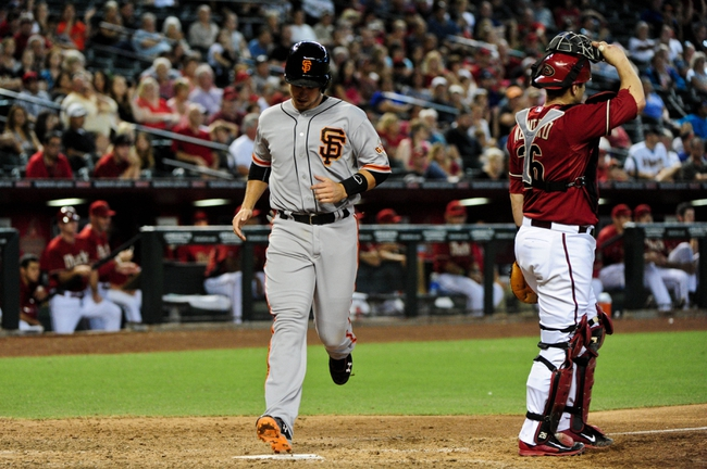 Jun 22, 2014; Phoenix, AZ, USA; San Francisco Giants catcher Buster Posey (28) scores on a hit by shortstop Brandon Crawford (35) as Arizona Diamondbacks catcher Miguel Montero (26) looks on during the ninth inning at Chase Field. Mandatory Credit: Matt Kartozian-USA TODAY Sports