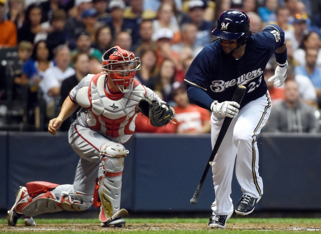 Jun 23, 2014; Milwaukee, WI, USA;   Milwaukee Brewers second baseman Rickie Weeks (23) runs to first base after a dropped third strike before being thrown out by Washington Nationals catcher Jose Lobaton (59) in the fifth inning at Miller Park. Mandatory Credit: Benny Sieu-USA TODAY Sports