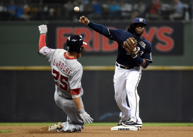 Jun 23, 2014; Milwaukee, WI, USA;   Milwaukee Brewers second baseman Rickie Weeks (23) completes a double play after forcing out Washington Nationals first baseman Adam LaRoche (25) in the eighth inning at Miller Park. Mandatory Credit: Benny Sieu-USA TODAY Sports