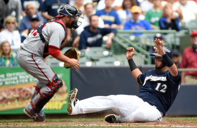 Jun 25, 2014; Milwaukee, WI, USA;  Milwaukee Brewers catcher Martin Maldonado (12) scores on a base hit by second baseman Scooter Gennett (not pictured) as Washington Nationals catcher Sandy Leon (41) waits for the throw in the sixth inning at Miller Park. Mandatory Credit: Benny Sieu-USA TODAY Sports