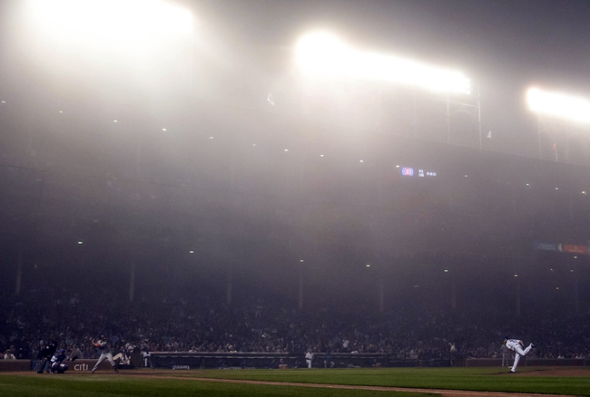 Jun 26, 2014; Chicago, IL, USA; Chicago Cubs starting pitcher Travis Wood (37) throws against Washington Nationals catcher Wilson Ramos (40) in the seventh inning under heavy fog during a game at Wrigley Field. The Chicago Cubs beat the Washington Nationals 5-3. Mandatory Credit: Jon Durr-USA TODAY Sports