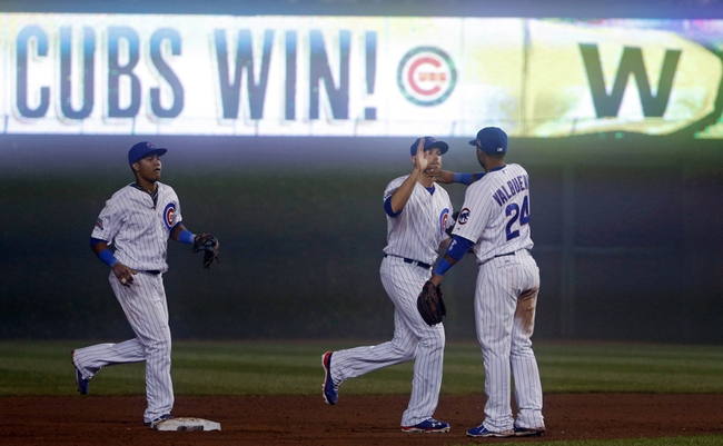 Jun 26, 2014; Chicago, IL, USA; Chicago Cubs right fielder Nate Schierholtz (center) high fives third baseman Luis Valbuena (24) after the final out in the ninth inningagainst the Washington Nationals during a game at Wrigley Field. The Chicago Cubs beat the Washington Nationals 5-3. Mandatory Credit: Jon Durr-USA TODAY Sports