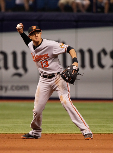 Jun 18, 2014; St. Petersburg, FL, USA; Baltimore Orioles third baseman Manny Machado (13) throws the ball to first for an out during the eighth inning against the Tampa Bay Rays at Tropicana Field. Baltimore Orioles defeated the Tampa Bay Rays 2-0. Mandatory Credit: Kim Klement-USA TODAY Sports