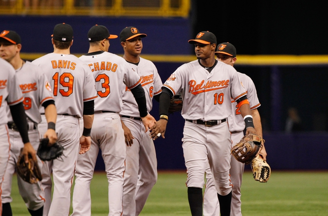 Jun 18, 2014; St. Petersburg, FL, USA; Baltimore Orioles center fielder Adam Jones (10) and teammates congratulate each other after they beat the Tampa Bay Rays at Tropicana Field. Baltimore Orioles defeated the Tampa Bay Rays 2-0. Mandatory Credit: Kim Klement-USA TODAY Sports