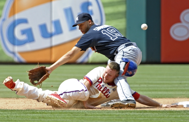 Jun 29, 2014; Philadelphia, PA, USA; Philadelphia Phillies third baseman Cody Asche (25) dives back into second base as ball gets away from Atlanta Braves shortstop Andrelton Simmons (19) during the sixth inning at Citizens Bank Park. The Braves won 3-2. Mandatory Credit: Eric Hartline-USA TODAY Sports