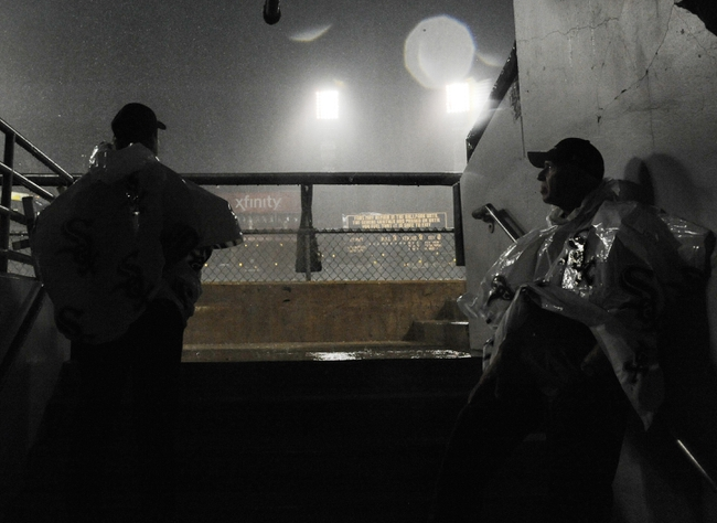 Jun 30, 2014; Chicago, IL, USA;  Security persons watch the field after the game between the Chicago White Sox and the Los Angeles Angels was cancelled due to severe weather at U.S Cellular Field. Mandatory Credit: David Banks-USA TODAY Sports