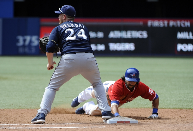 Jul 1, 2014; Toronto, Ontario, CAN; Toronto Blue Jays player Darin Mastoianni (33) dives back to first base watched by Brewers first basement Lyle Overbay (24) during the 8th inning at Rogers Centre. Mandatory Credit: Peter Llewellyn-USA TODAY Sports