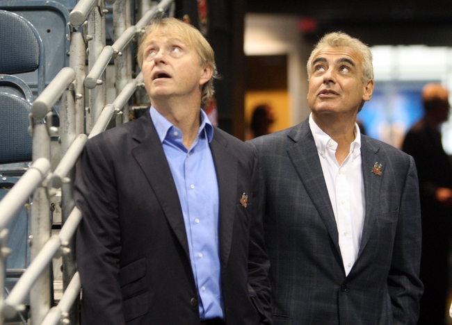 Jul 2, 2014; Milwaukee, WI, USA; Milwaukee Bucks co-owners Wesley Edens (left) and Marc Lasry look at the jumbotron as it display graphic to welcome new coach Jason Kidd at the BMO Harris Bradley Center. Mandatory Credit: Mary Langenfeld-USA TODAY Sports