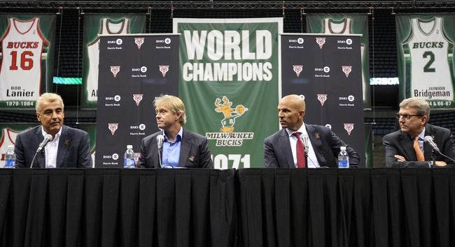 Jul 2, 2014; Milwaukee, WI, USA; Milwaukee Bucks co-owner Marc Lasry (far left) speaks to the press during a news conference featuring new head coach Jason Kidd at the BMO Harris Bradley Center. From left:  Marc Lasry, co-owner Wesley Edens, new head coach Jason Kidd and general manager John Hammond.  Mandatory Credit: Mary Langenfeld-USA TODAY Sports
