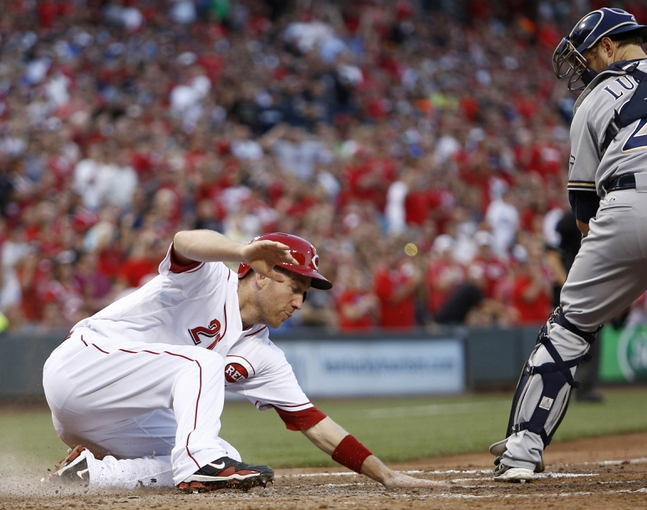 Jul 4, 2014; Cincinnati, OH, USA; Cincinnati Reds third baseman Todd Frazier (21) scores a run past Milwaukee Brewers catcher Jonathan Lucroy (20) during the fifth inning at Great American Ball Park. Mandatory Credit: David Kohl-USA TODAY Sports