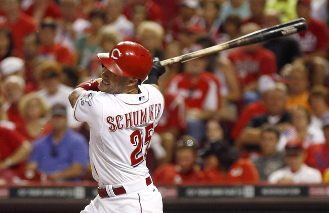 Jul 4, 2014; Cincinnati, OH, USA; Cincinnati Reds right fielder Skip Schumaker hits a single against the Milwaukee Brewers during the eighth inning at Great American Ball Park.The Reds won 4-2. Mandatory Credit: David Kohl-USA TODAY Sports