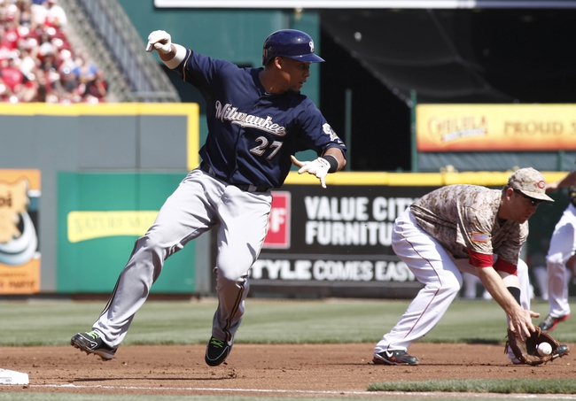 Jul 5, 2014; Cincinnati, OH, USA; Milwaukee Brewers center fielder Carlos Gomez (27) rounds the bases past Cincinnati Reds third baseman Todd Frazier, right, after a Kris Davis ground ball during the first inning at Great American Ball Park. Mandatory Credit: David Kohl-USA TODAY Sports