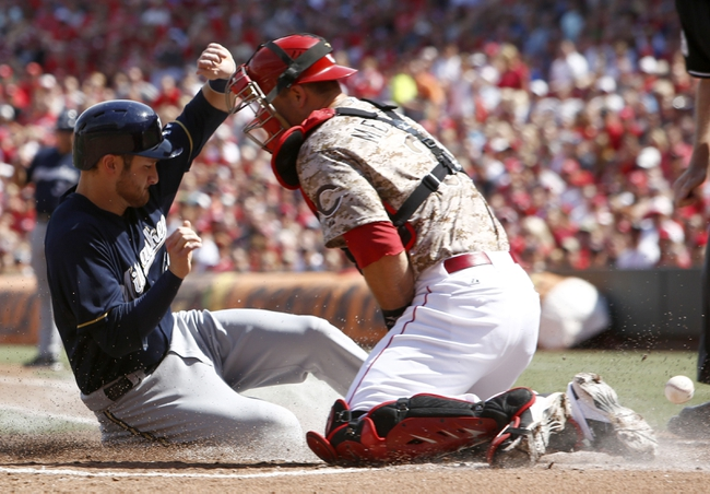 Jul 5, 2014; Cincinnati, OH, USA; Milwaukee Brewers catcher Jonathan Lucroy, left, scores at home ahead of Cincinnati Reds catcher Devin Mesoraco, right, during the first inning at Great American Ball Park. Mandatory Credit: David Kohl-USA TODAY Sports