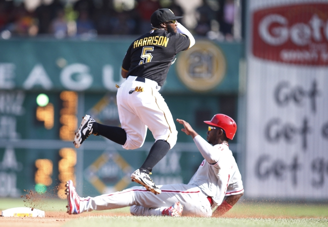 Jul 5, 2014; Pittsburgh, PA, USA; Pittsburgh Pirates second baseman Josh Harrison (5) turns a double play over Philadelphia Phillies left fielder Domonic Brown (R) during the fourth inning at PNC Park. Mandatory Credit: Charles LeClaire-USA TODAY Sports