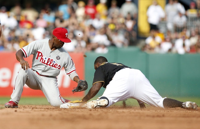 Jul 5, 2014; Pittsburgh, PA, USA; Philadelphia Phillies shortstop Jimmy Rollins (L) applies a late tag as Pittsburgh Pirates second baseman Josh Harrison (5) steals second base during the sixth inning at PNC Park. The Pirates won 3-2.Mandatory Credit: Charles LeClaire-USA TODAY Sports