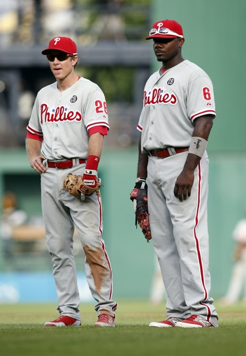Jul 5, 2014; Pittsburgh, PA, USA; Philadelphia Phillies second baseman Chase Utley (26) and first baseman Ryan Howard (6) wait out a pitching change against the Pittsburgh Pirates during the eighth inning at PNC Park. The Pirates won 3-2. Mandatory Credit: Charles LeClaire-USA TODAY Sports