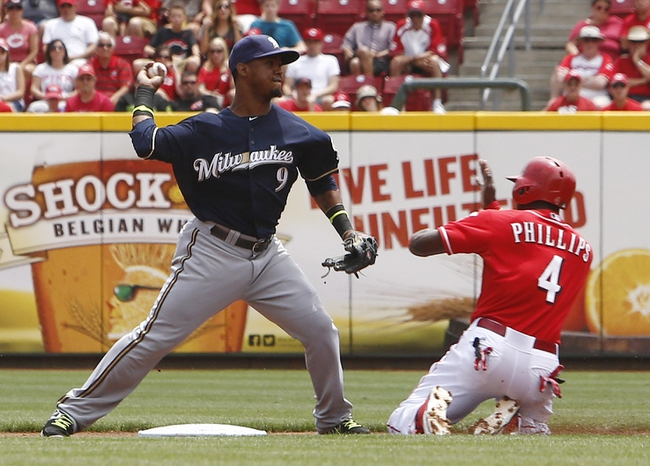 Jul 6, 2014; Cincinnati, OH, USA; Cincinnati Reds second baseman Brandon Phillips (4) is forced out at second base by Milwaukee Brewers shortstop Jean Segura (9) during the first inning at Great American Ball Park. Mandatory Credit: David Kohl-USA TODAY Sports