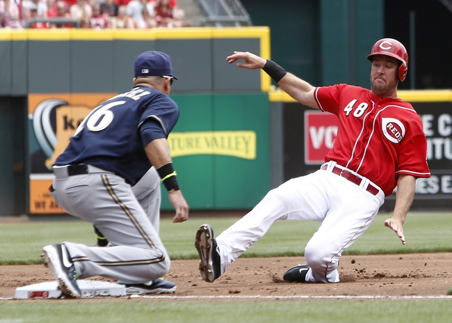 Jul 6, 2014; Cincinnati, OH, USA; Cincinnati Reds left fielder Ryan Ludwick (48) is tagged out at third base by Milwaukee Brewers third baseman Aramis Ramirez (16) during the first inning at Great American Ball Park. Mandatory Credit: David Kohl-USA TODAY Sports