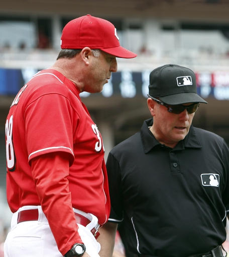 Jul 6, 2014; Cincinnati, OH, USA; Cincinnati Reds manager Bryan Price (left) talks with first base umpire Jerry Meals (right) over a fan interference call during the second inning at Great American Ball Park. Mandatory Credit: David Kohl-USA TODAY Sports