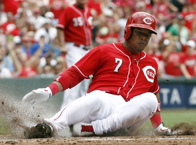 Jul 6, 2014; Cincinnati, OH, USA; Cincinnati Reds shortstop Ramon Santiago (7) slides into home plate but is called out due to fan interference in right during the second inning against the Milwaukee Brewers at Great American Ball Park. Mandatory Credit: David Kohl-USA TODAY Sports