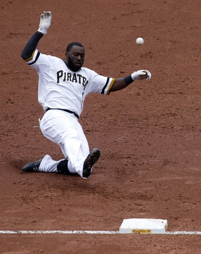 Jul 6, 2014; Pittsburgh, PA, USA; Pittsburgh Pirates left fielder Josh Harrison (5) beats the ball to third base for a triple against the Philadelphia Phillies during the third inning at PNC Park. Mandatory Credit: Charles LeClaire-USA TODAY Sports