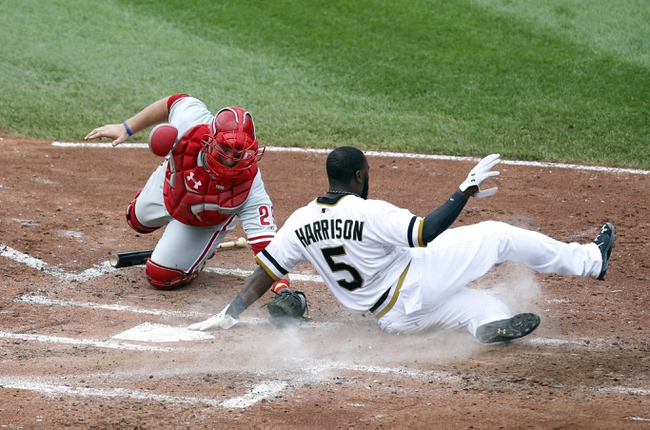 Jul 6, 2014; Pittsburgh, PA, USA; Pittsburgh Pirates left fielder Josh Harrison (5) slides home to score ahead of a tag by Philadelphia Phillies catcher Cameron Rupp (29) during the third inning at PNC Park. Mandatory Credit: Charles LeClaire-USA TODAY Sports