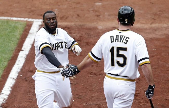 Jul 6, 2014; Pittsburgh, PA, USA; Pittsburgh Pirates left fielder Josh Harrison (5) is greeted by first baseman Ike Davis (15) after Harrison scored a run against the Philadelphia Phillies during the third inning at PNC Park. Mandatory Credit: Charles LeClaire-USA TODAY Sports