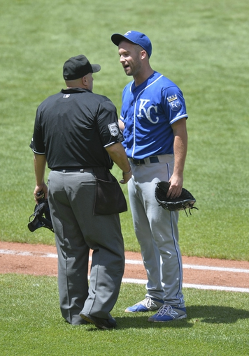 Jul 6, 2014; Cleveland, OH, USA; Kansas City Royals starting pitcher Danny Duffy (41) talks with home plate umpire Eric Cooper (56) in the third inning at Progressive Field. Mandatory Credit: David Richard-USA TODAY Sports