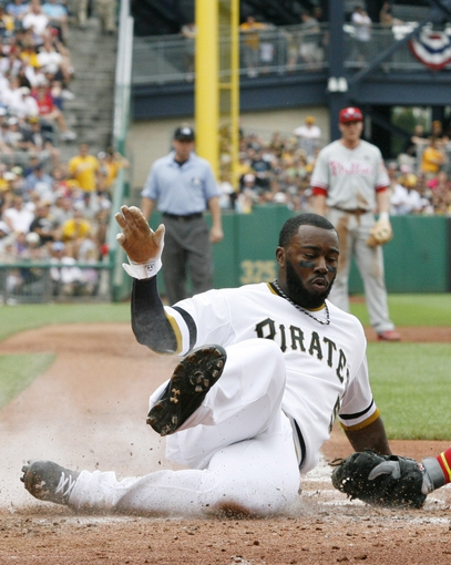 Jul 6, 2014; Pittsburgh, PA, USA; Pittsburgh Pirates left fielder Josh Harrison (5) slides home to score ahead of a tag by Philadelphia Phillies catcher Cameron Rupp (not pictured) during the third inning at PNC Park. The Pirates won 6-2. Mandatory Credit: Charles LeClaire-USA TODAY Sports