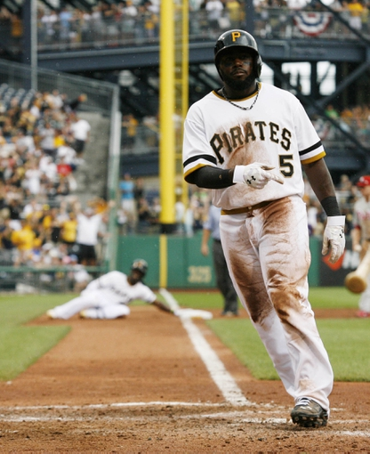 Jul 6, 2014; Pittsburgh, PA, USA; Pittsburgh Pirates right fielder Josh Harrison (5) crosses home plate to score on a triple by center fielder Andrew McCutchen (background left) against the Philadelphia Phillies during the eighth inning at PNC Park. The Pirates won 6-2. Mandatory Credit: Charles LeClaire-USA TODAY Sports