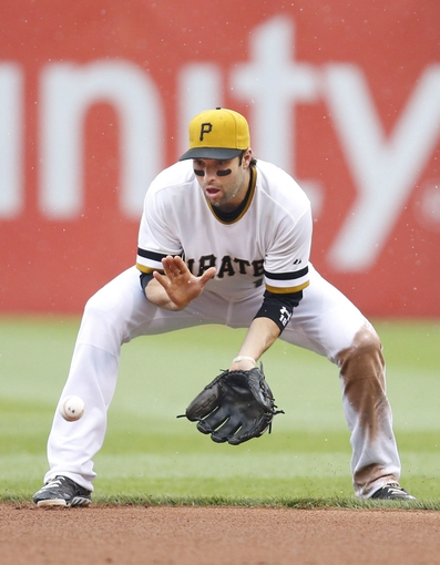Jul 6, 2014; Pittsburgh, PA, USA; Pittsburgh Pirates second baseman Neil Walker (18) fields a ground ball against the Philadelphia Phillies during the eighth inning at PNC Park. The Pirates won 6-2. Mandatory Credit: Charles LeClaire-USA TODAY Sports