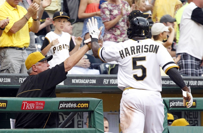 Jul 6, 2014; Pittsburgh, PA, USA; Pittsburgh Pirates manager Clint Hurdle (L) greets Pittsburgh Pirates left fielder Josh Harrison (5) at the dugout after Harrison scored a run against the Philadelphia Phillies during the eighth inning at PNC Park. The Pirates won 6-2. Mandatory Credit: Charles LeClaire-USA TODAY Sports