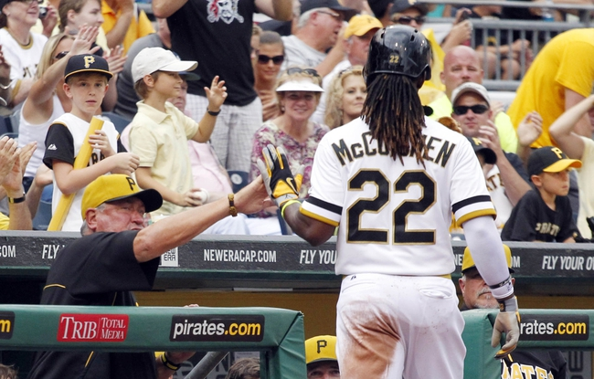 Jul 6, 2014; Pittsburgh, PA, USA; Pittsburgh Pirates manager Clint Hurdle (left) greets center fielder Andrew McCutchen (22) at the dugout after McCutchen scored a run against the Philadelphia Phillies during the eighth inning at PNC Park. The Pirates won 6-2. Mandatory Credit: Charles LeClaire-USA TODAY Sports