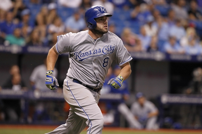 Jul 7, 2014; St. Petersburg, FL, USA; Kansas City Royals third baseman Mike Moustakas (8) hits a sacrifice fly ball during the eighth inning against the Tampa Bay Rays at Tropicana Field. Mandatory Credit: Kim Klement-USA TODAY Sports