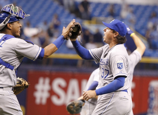 Jul 7, 2014; St. Petersburg, FL, USA; Kansas City Royals catcher Salvador Perez (13) and relief pitcher Scott Downs (37) congratulate each other after they beat the Tampa Bay Rays at Tropicana Field. Kansas City Royals defeated the Tampa Bay Rays 6-0.  Mandatory Credit: Kim Klement-USA TODAY Sports