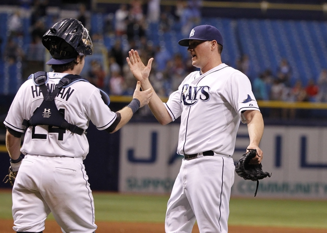 Jul 8, 2014; St. Petersburg, FL, USA; Tampa Bay Rays relief pitcher Jake McGee (57) and catcher Ryan Hanigan (24) congratulate each other after they beat the Kansas City Royals at Tropicana Field. Tampa Bay Rays defeated the Kansas City Royals 4-3. Mandatory Credit: Kim Klement-USA TODAY Sports