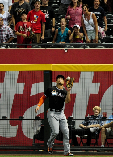 Jul 8, 2014; Phoenix, AZ, USA; Miami Marlins right fielder Giancarlo Stanton (27) catches a ball hit by Arizona Diamondbacks shortstop Cliff Pennington (4) to end the game and beat the Diamondbacks 2-1 at Chase Field. Mandatory Credit: Matt Kartozian-USA TODAY Sports