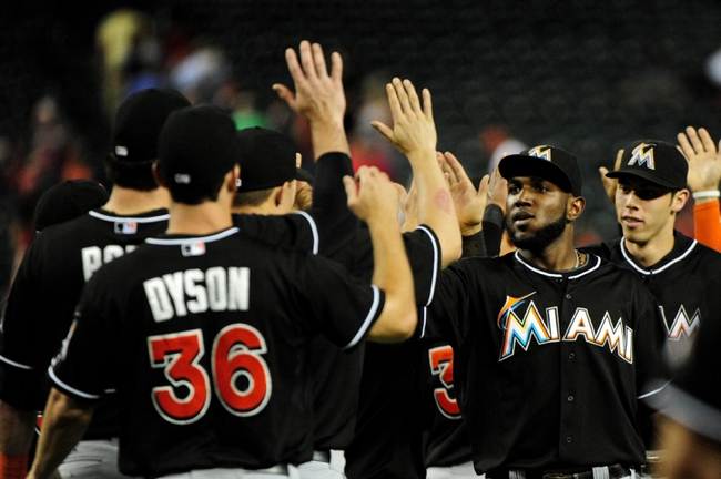 Jul 8, 2014; Phoenix, AZ, USA; Miami Marlins center fielder Marcell Ozuna (13) celebrates with teammates after beating the Arizona Diamondbacks 2-1 at Chase Field. Mandatory Credit: Matt Kartozian-USA TODAY Sports