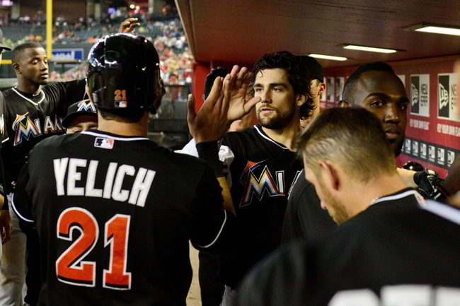 Jul 9, 2014; Phoenix, AZ, USA; Miami Marlins left fielder Christian Yelich (21) celebrates with teammates after scoring on a sacrifice fly by right fielder Giancarlo Stanton (not pictured) during the sixth inning against the Arizona Diamondbacks at Chase Field. Mandatory Credit: Matt Kartozian-USA TODAY Sports