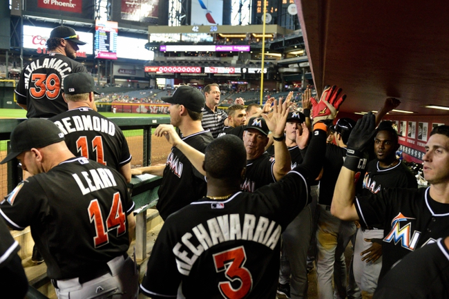 Jul 9, 2014; Phoenix, AZ, USA; Miami Marlins shortstop Adeiny Hechavarria (3) celebrates with teammates after scoring on a double by second baseman Donovan Solano (not pictured) in the tenth inning against the Arizona Diamondbacks at Chase Field. Mandatory Credit: Matt Kartozian-USA TODAY Sports